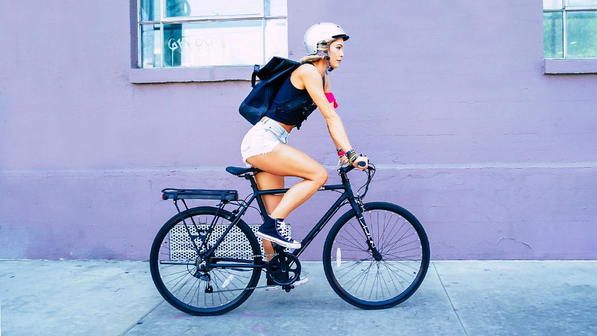 Woman wearing helmet and carrying backpack riding an EB12 eBike for Fitness.