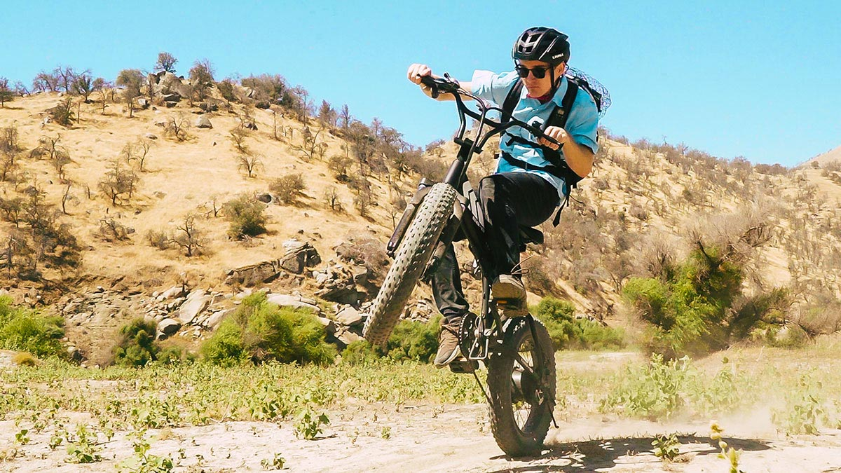 Close-up of man popping a wheelie while trail riding on an EB8 e-mtn bike.