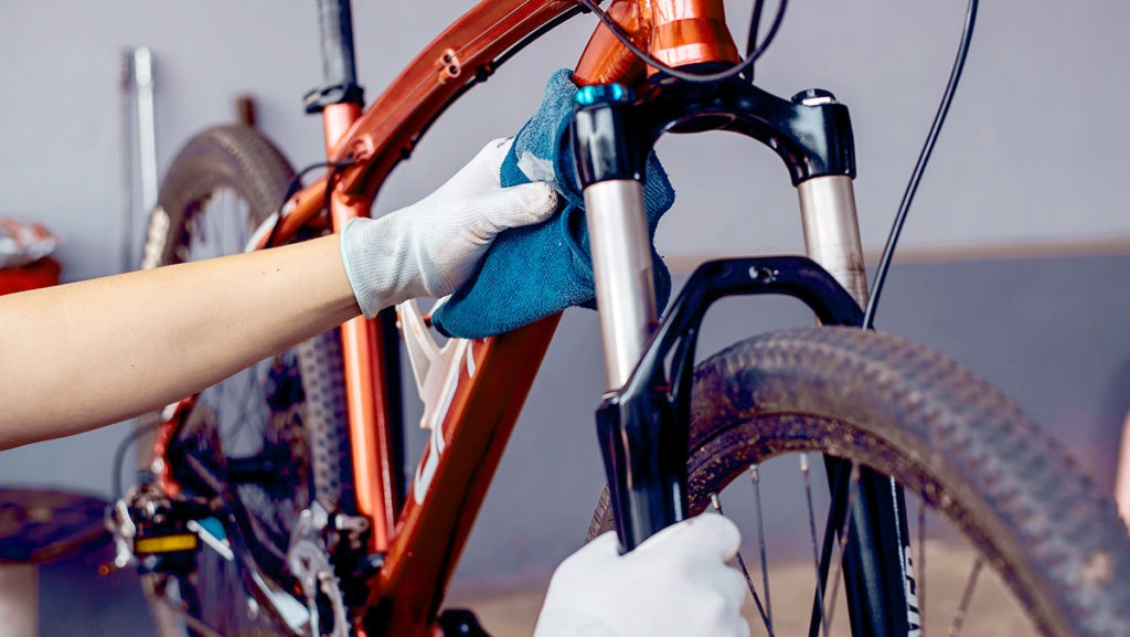 Close-up of an older bike being dried with non-abrasive cloth before being put into storage.