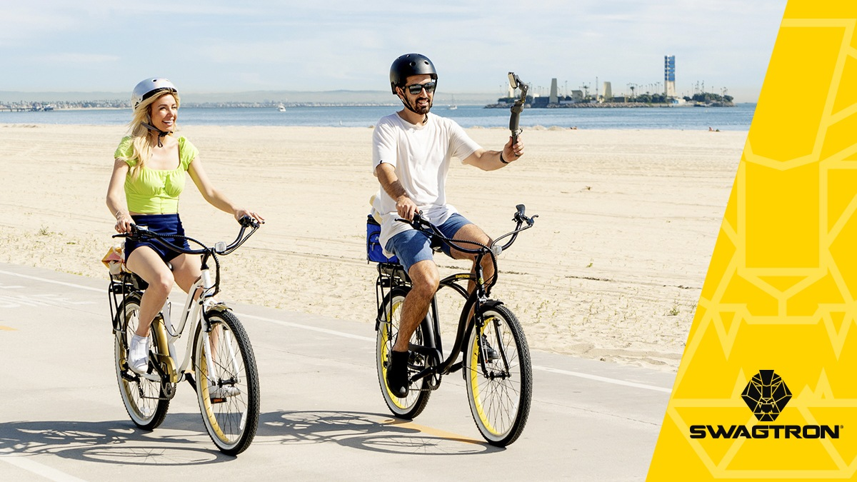Happy couple wearing helmets, riding their electric bikes along the beachside boardwalk.