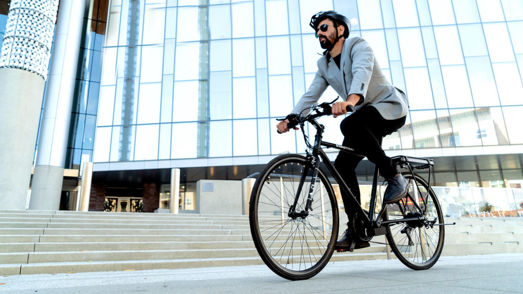 Man wearing a suit and helmet commuting to work on an EB12 eBike