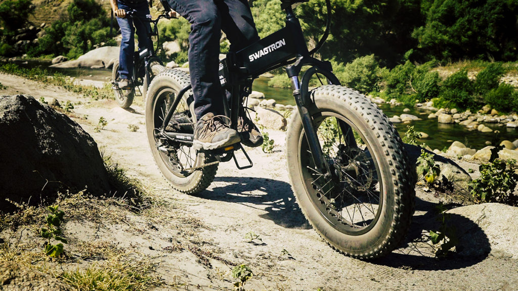 Close up of two people riding their EB8 Fat-Tire eBikes on a rugged dirt trail.