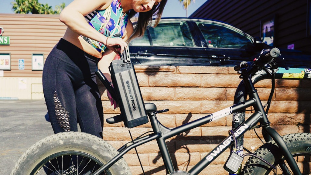 Young woman changes the battery of her EB6 Fat-Tire eBike.