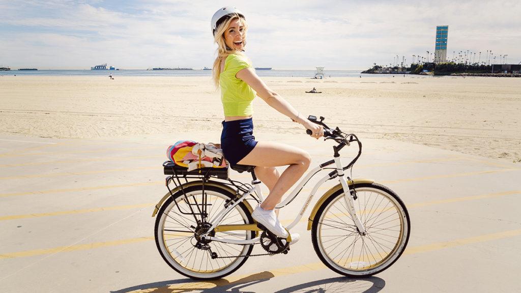 Smiling woman wearing a helmet riding the EB10 Step-Through Cruiser electric bike.