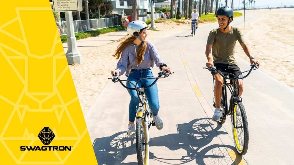 Couple wearing helmets riding their EB11 and EB10 eBikes on the boardwalk next to the beach.