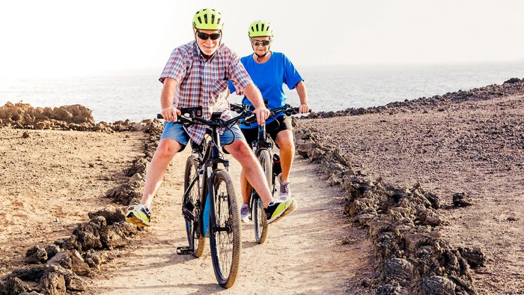 Older couple outside riding electric bikes on a dirt trail.