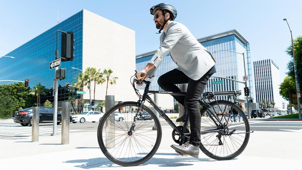 Man wearing a helmet riding an EB12 Road eBike from SWAGTRON.