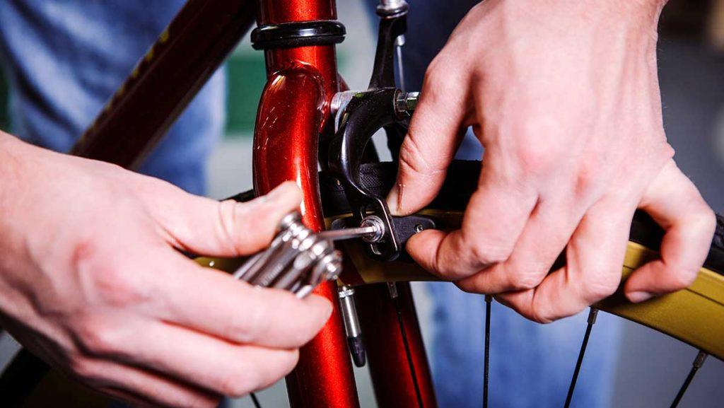 Close-up of someone using an Allen wrench to tighten the brakes of a standard bicycle.