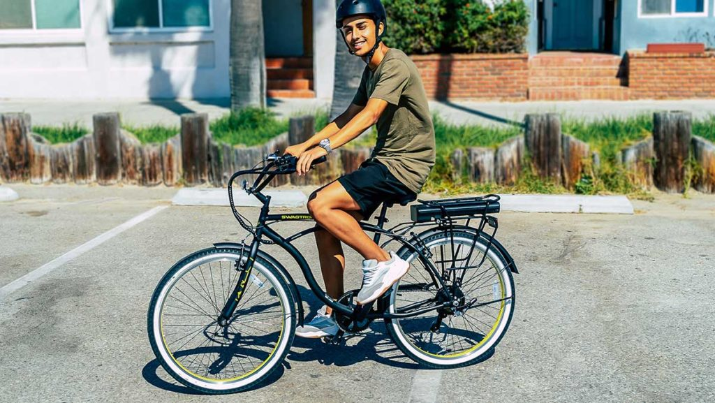 Young man wearing helmet riding the EB11 7-speed Cruiser eBike with Removable Battery.