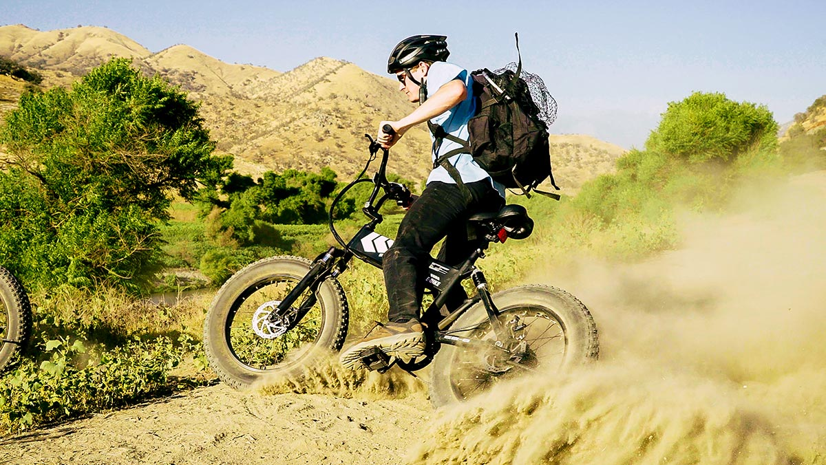 Man wearing helmet, carrying backpack, and trail riding on his EB8 All-Terrain eBike.