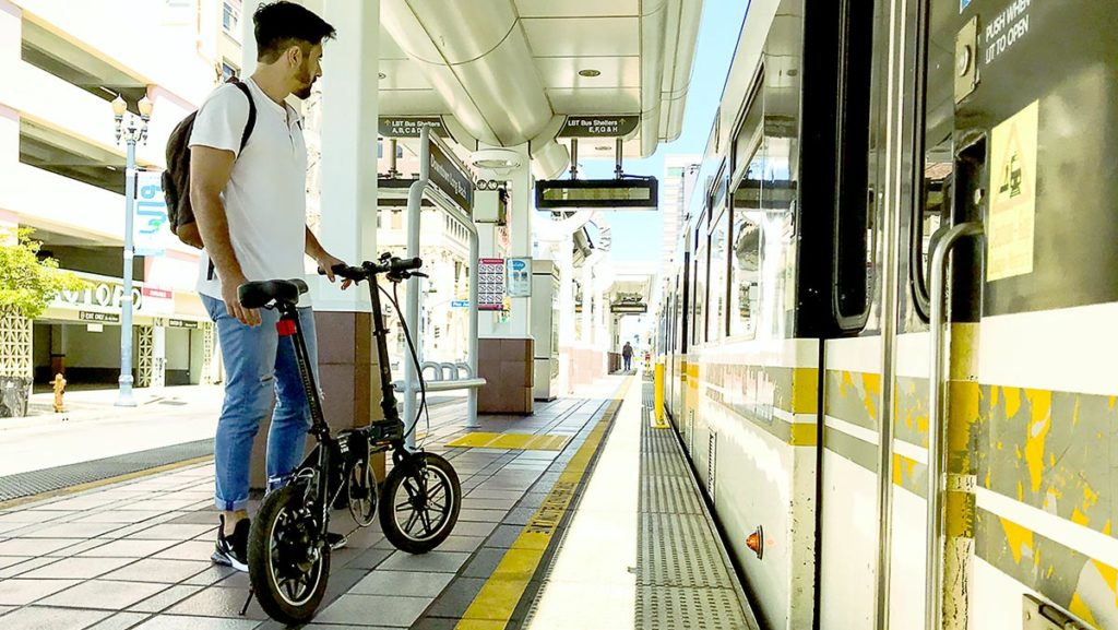 Young man standing with his EB5 Pro electric bike, waiting for the train.