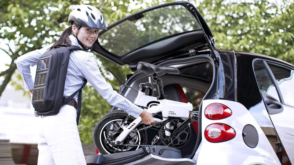 Woman putting her folded electric bike - EB5 Pro in the trunk of her electric car.