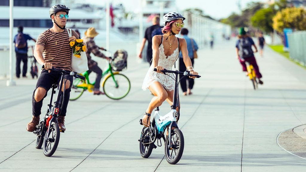 Couple wearing helmets, riding their EB7 electric bike from SWAGTRON.