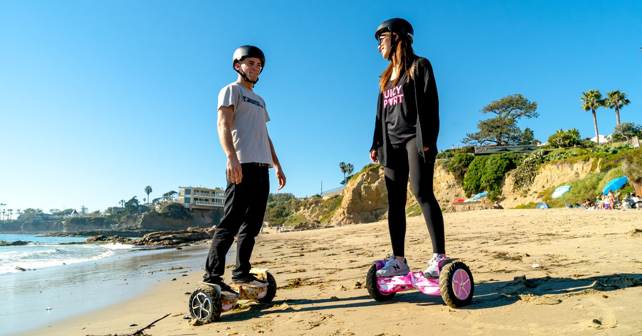 A couple wearing helmets riding on T6 hoverboards on the beach.