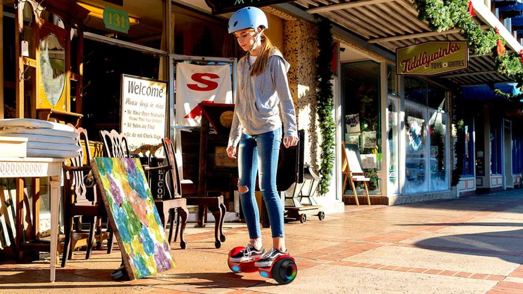 Girl wearing a helmet and riding on the swagBOARD Twist Remix Hoverboard