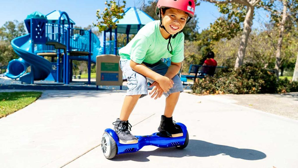 Happy kid wearing a helmet and riding a swagBOARD Twist.