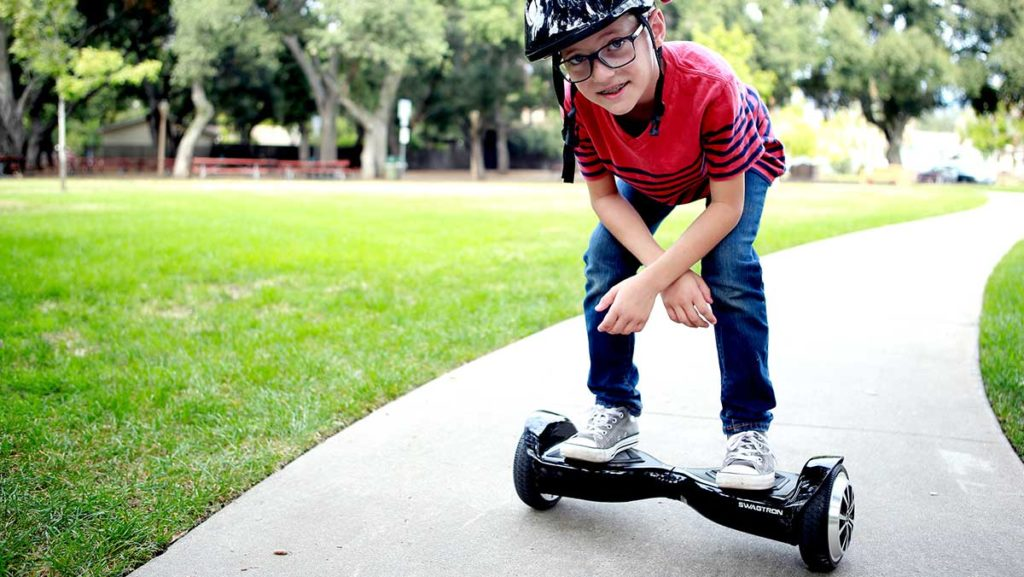Kid wearing a helmet and riding the swagBOARD T5.
