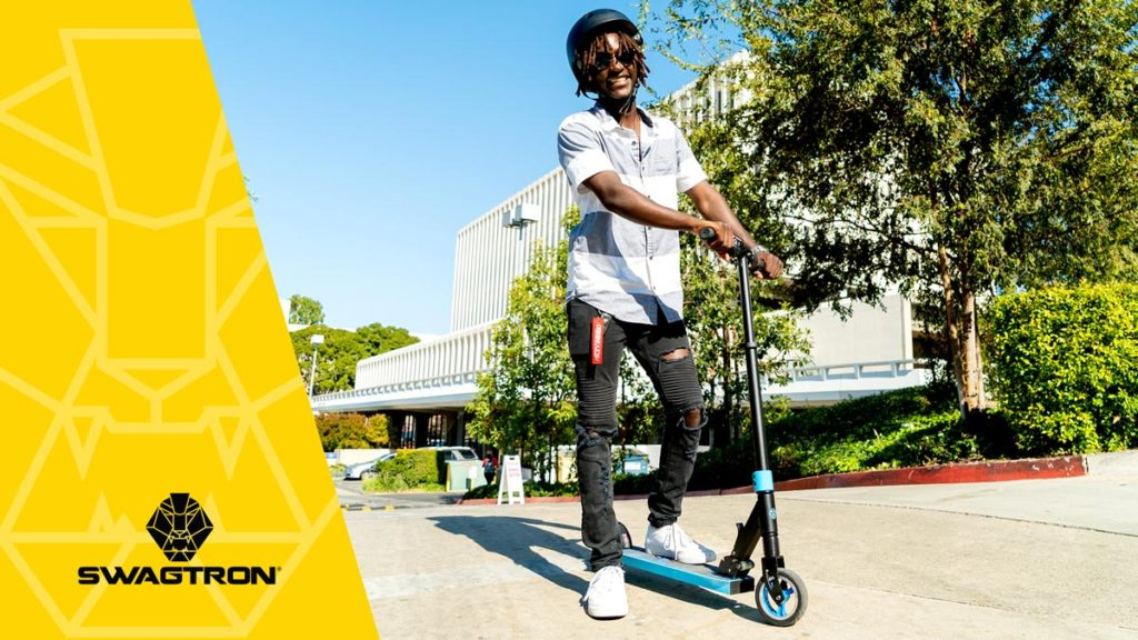 ALT: Guy wearing a helmet standing with his Swagger 8 Foldable eScooter on campus.