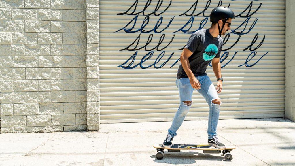 Man wearing a helmet riding an NG2 Electric Skateboard.