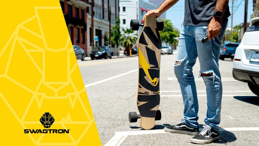 Man standing, holding an NG2 Electric Longboard.