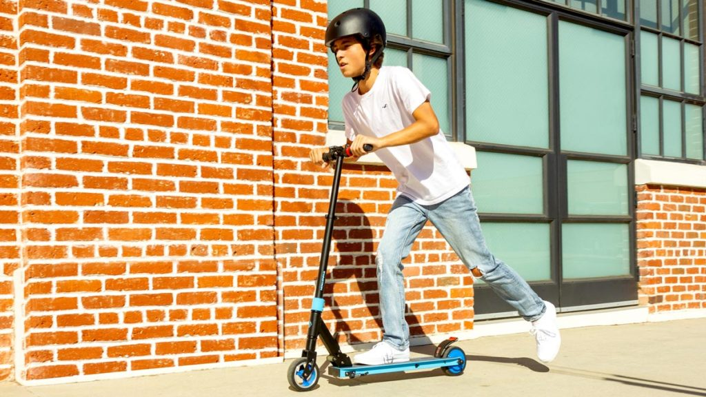 Kid wearing a helmet riding on a Swagger 8 electric scooter.