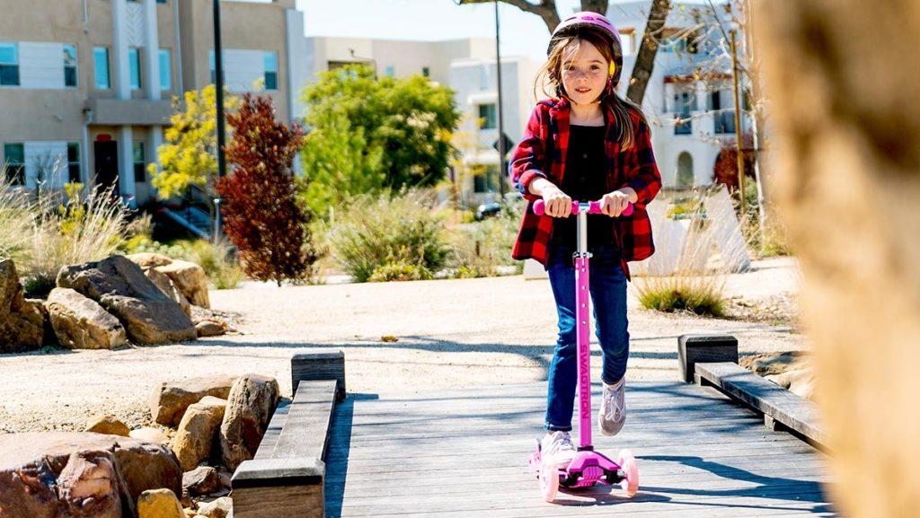 Girl wearing helmet riding a K5 3-wheeled light-up kick scooter.
