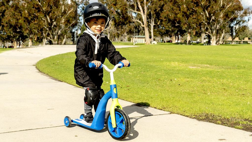 Young boy toddler wearing a helmet, riding on a K6 4-in-1 ride-on scooter.