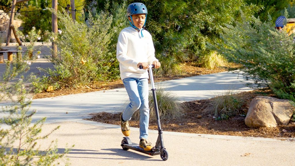 Teen boy wearing a helmet and riding on a Swagger SK3 Glide.