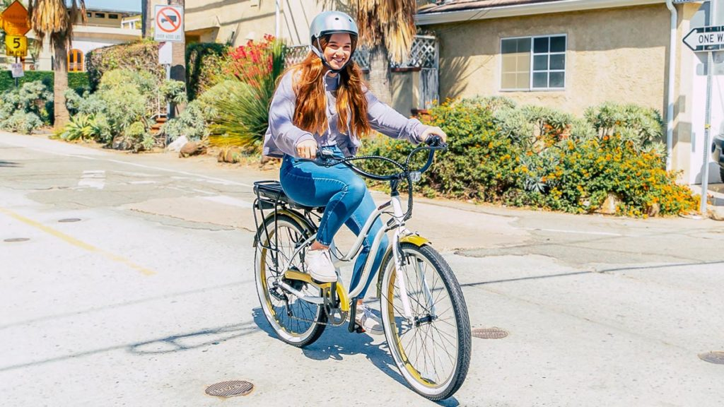 Young woman wearing a helmet riding a white EB9 Step-Through Electric City Bike.