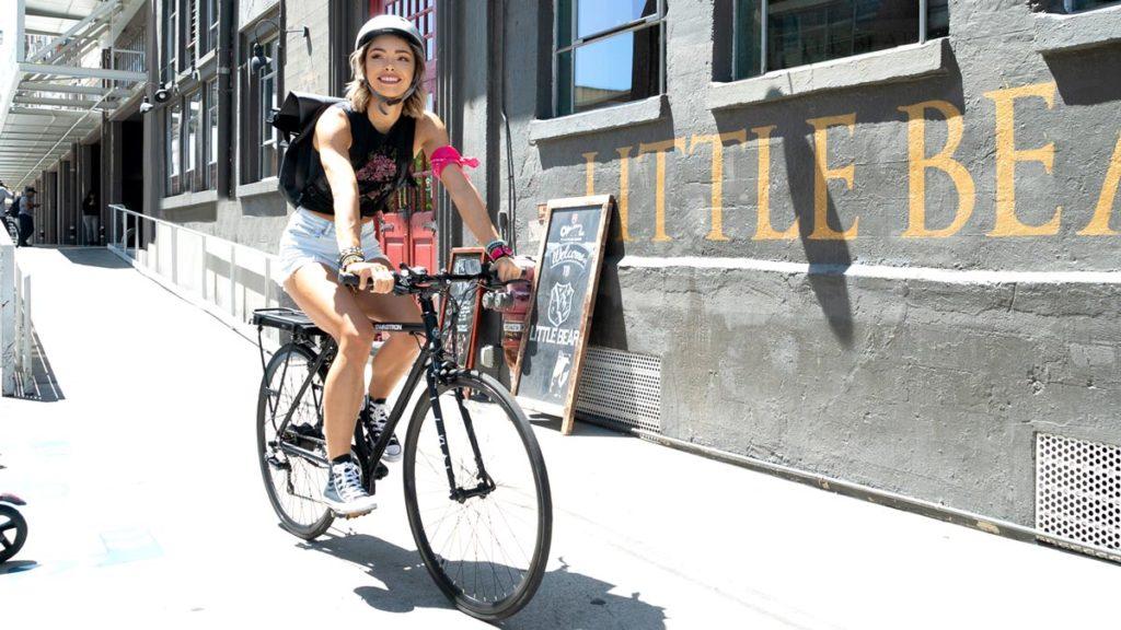 Woman wearing a helmet riding an EB12 electric bike on the sidewalk.