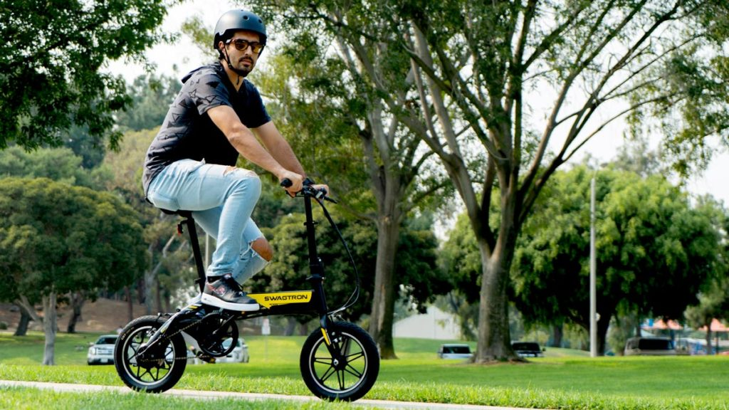 Guy wearing sunglasses and helmet riding an EB5 Pro Plus eBike in the park.