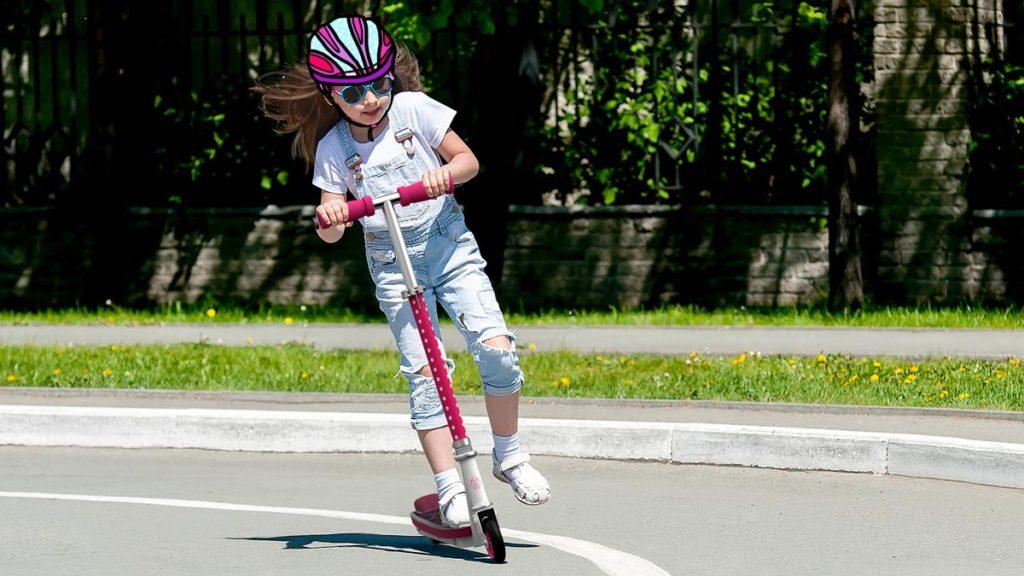 Girl wearing helmet riding an SK1 Kick-Start Scooter.