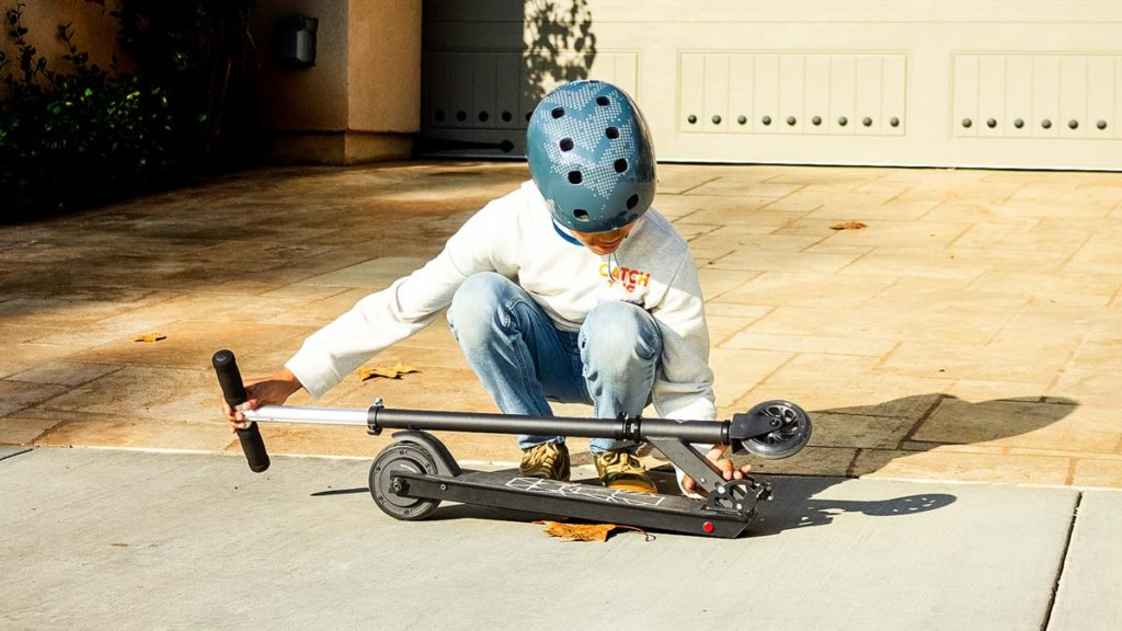 Young pre-teen boy folding down the SK3 Glide.
