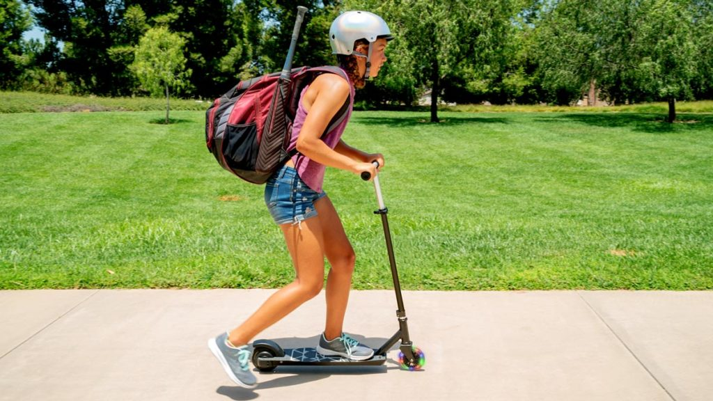 Younger pre-teen girl wearing a backpack and helmet riding a Metro SK3 electric scooter.