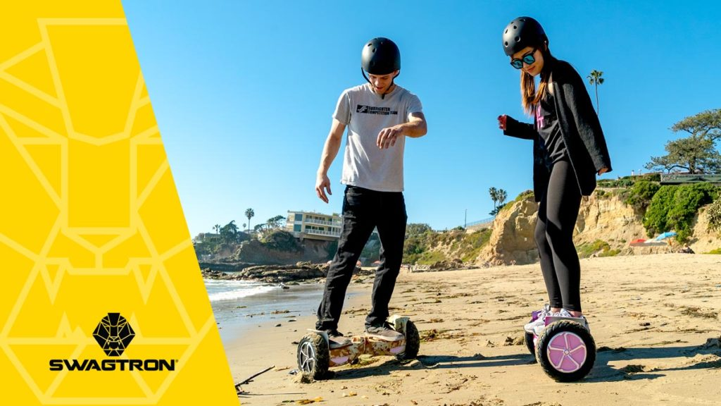 Guy and girl on the beach wearing helmets and riding the swagBOARD T6 hoverboard.
