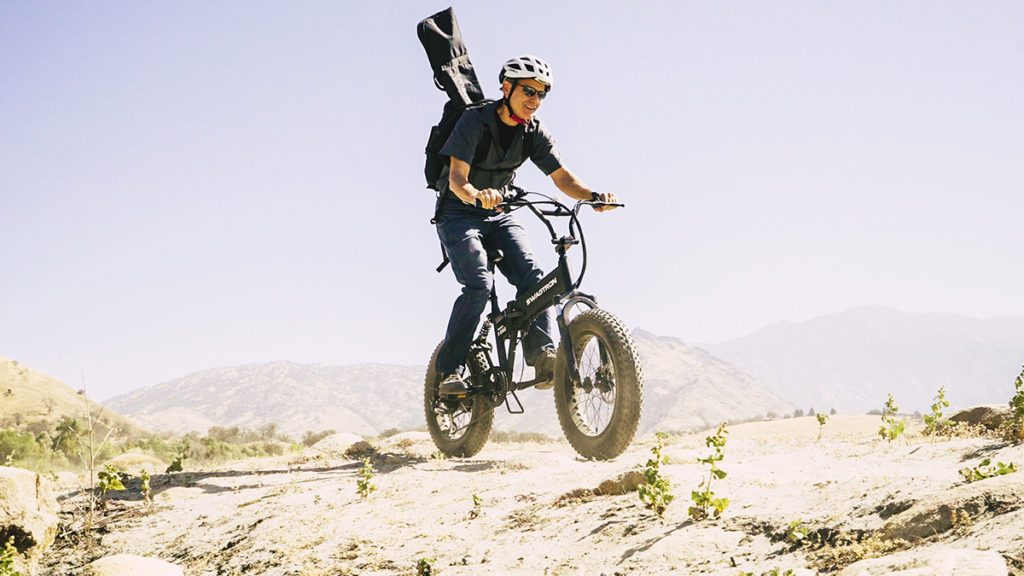 Man wearing a helmet riding an EB8 Fat Tire eBike off road.