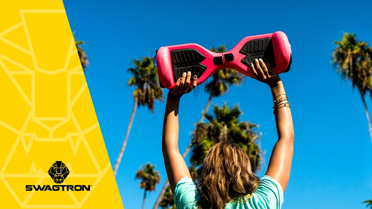 Young girl holding up a SWAGTRON hoverboard over her head.