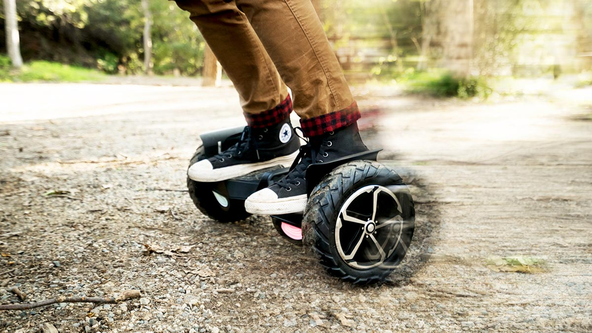 Guy riding the swagBOARD T6 hoverboard on gravel.