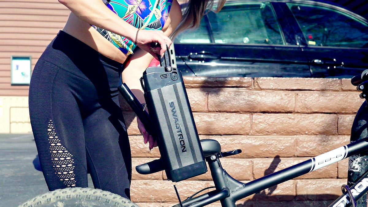 Woman pulling out the removable battery on her EB6 Fat-Tire eBike.