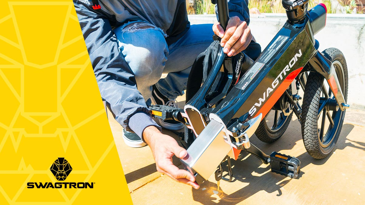 Close-up of a guy removing the battery from an SWAGTRON electric bike.