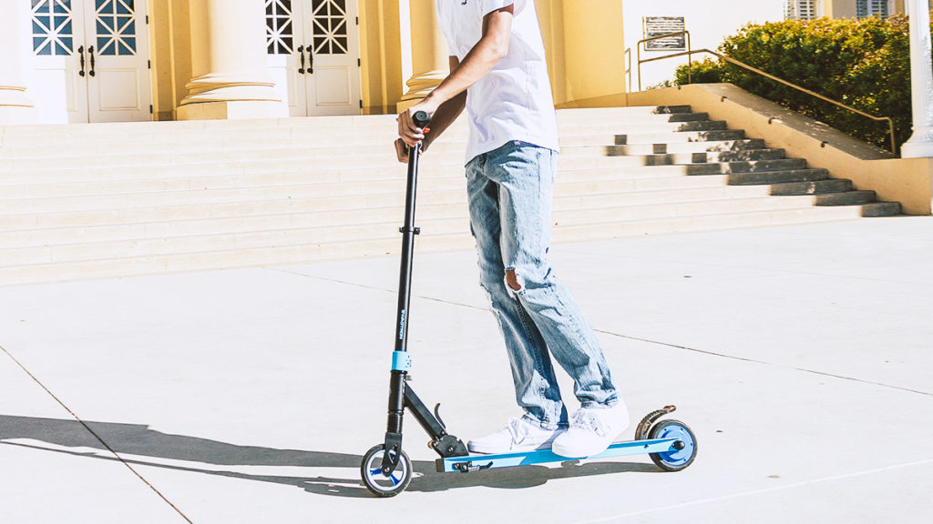 Guy riding on the Swagger 8 Electric Scooter for Kids and Teens.