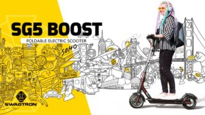 Young woman riding her Swagger 5 Boost in front of a mural illustration by Pretty Done