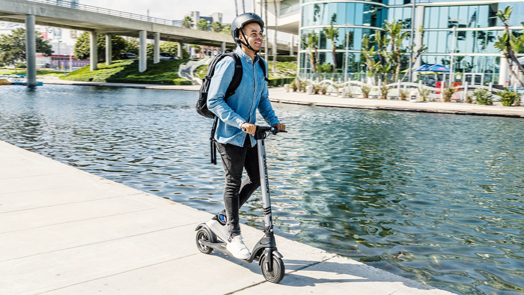 Man wearing helmet riding the Swagger 7 electric scooter.
