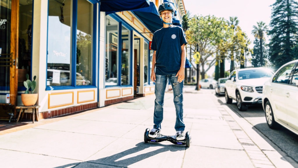 Boy wearing helmet riding a swagBOARD hoverboard.