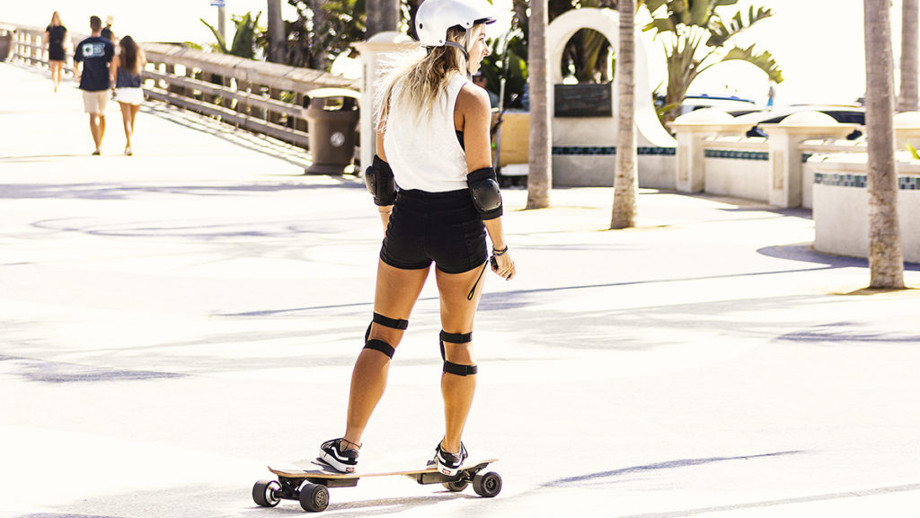 Woman wearing helmet and elbow- & kneepads riding on the NG2 electric longboard.