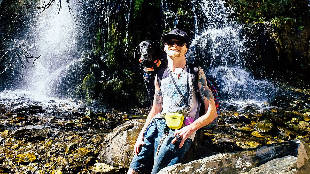 Jonah Vandever with dog in front of a waterfall.