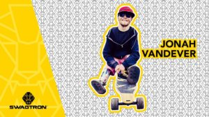 Jonah Vandever sitting on the NG2 electric longboard
