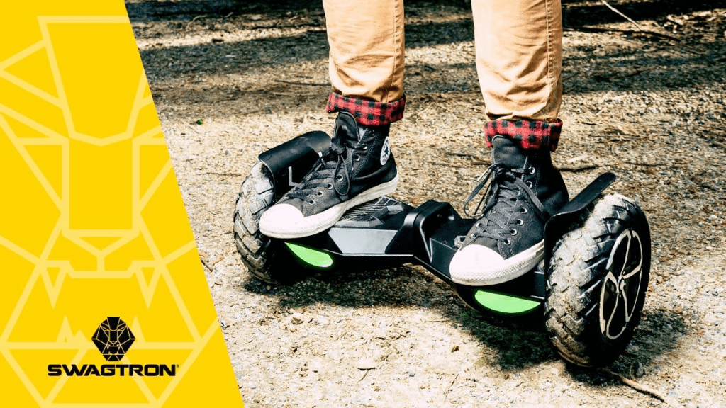Closeup of someone standing on a black T8 hoverboard on a dirt trail.