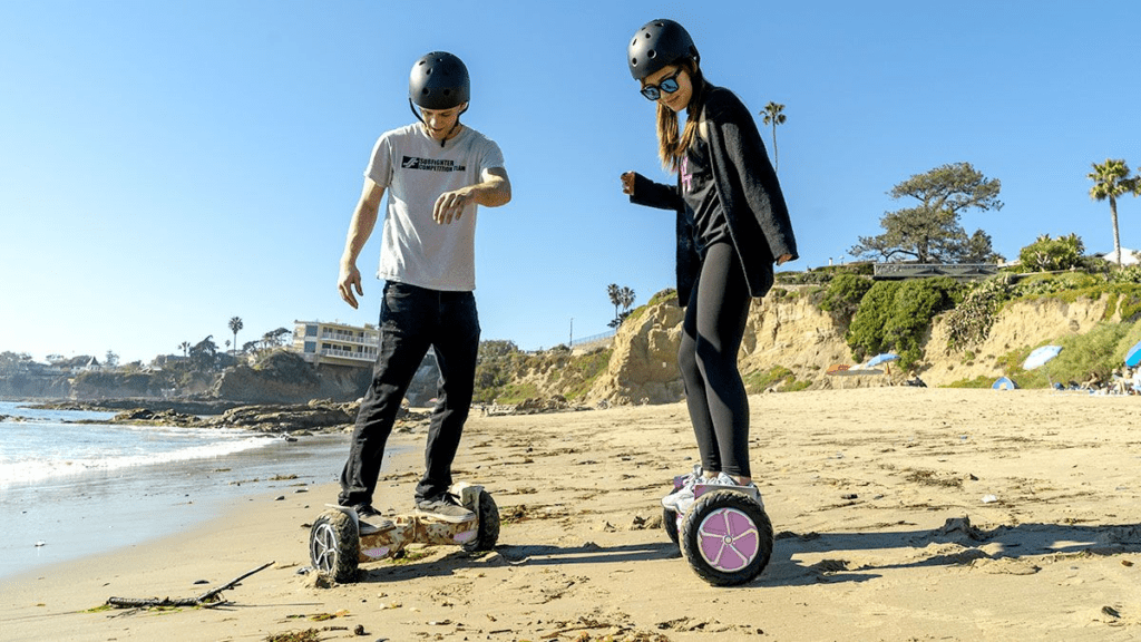 Guy and girl wearing helmets riding the T6 hoverboard on a beach.