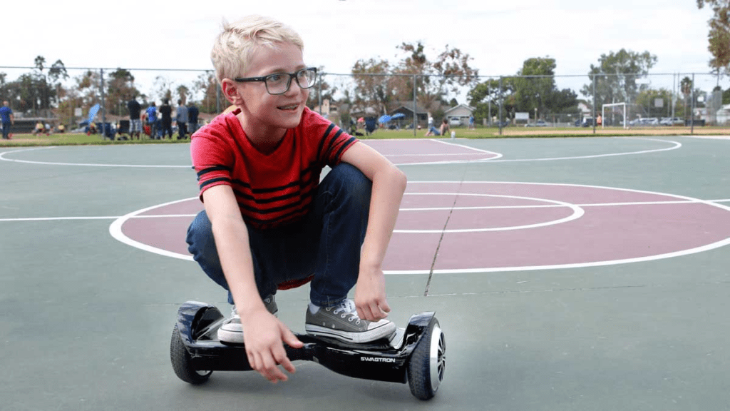 Young teen squatting on his swagBOARD T5 Classic hoverboard.